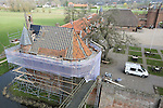 Foto: VidiPhoto<br /> <br /> DOORNENBURG - Dakspecialisten van timmer- en aannemingsbedrijf De Vries uit Hummelo, werken woensdag aan een van de meest lastigste klussen ooit. De scheve slotkapel van kasteel Doornenburg krijgt een nieuw dak en het kost veel creativiteit om alles passend en waterdicht te krijgen. De slotkapel van het bekende kasteel van Floris wordt nog wekelijks gebruikt voor bruiloften, maar staat flink uit het lood. Tussen de linker- en rechterzijde van het dak zit 50 centimeter verloop, met bovendien een knik in het midden van het dak. Dat betekent dat ook de panlatten scheef gemonteerd moeten worden. Bovendien heeft de voorzijde van de kapel supersmalle dakpannen, die vrijwel nergens meer te krijgen zijn. Behalve nieuwe dakpannen en panlatten, moet een een deel van het dakbeschot vernieuwd worden. De werkzaamheden duren in totaal zo'n vier weken. Het herstel van de daken van de voorburcht en slotkapel kost ruim 70.000 euro. Een deel daarvan wordt betaald door de gemeente Lingewaard. Kasteel Doornenburg is een rijksmonument en het enige kasteel in Nederland met een nog werkzame boerderij op de voorburcht.