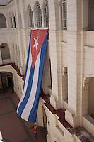 Cuba l'Avana , cortile del Museo della rivoluzione, una persona passa sotto una grande bandiera cubana