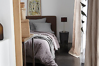 A small bedroom is furnished with a contemporary bed draped in natural linen sheets