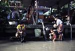 A family baths in a klong. People live on the klongs, boulevards of water that flow through the city like open veins,  and spend their lifetimes living in houseboats in Bangkok, Thailand. (Jim Bryant Photo)