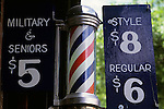 Barber shop sign with barber pole and dollar amounts in University District Seattle Washington State .