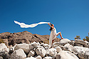 Beautiful asian woman in white holding a blowing scarf in a dramatic landscape.