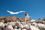 Beautiful asian woman in white holding a blowing scarf in a dramatic landscape.<br />