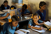 Students in class at the Government Girls High School, Venugopalapuram in Cuddalore...Cuddalore's Government Girls High School is under-resourced with some student forced to sit on the floor for want of a desk. Though most classrooms are housed in a building that is only two years old, there is little ventilation to lessen the effects Cuddalore's tropical heat. The school does offer extra &quot;`bridge&quot; classes for those students recently arrived from village schools but staff are frequently absent from the school...Photo: Tom Pietrasik.Cuddalore, Tamil Nadu. India.October 7th 2009