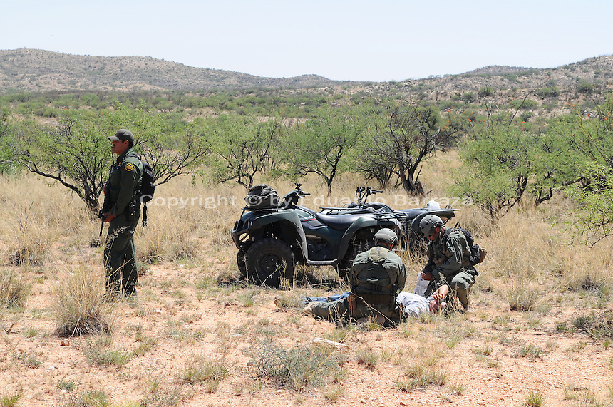 Sasabe, Arizona – Border Patrol Search, Trauma, and Rescue Unit (BORSTAR) agents perform a rescue drill in the Arizona desert near Sasabe to highlight the risks border-crossers face when entering the U.S. illegally. BORSTAR is a specialized unit that responds to emergency search and rescue situations. U.S. Customs Border Protection (CBP) transported journalists to this remote area where they walked through a 1.3 miles trail during a two-day event organized by the Tucson Sector Border Patrol. The event brought national and international journalists to the Arizona desert to become acquainted with the dynamics of this area. This area is located near the Sasabe Port of Entry, a border-crossing station located in southern Arizona, and about 70 miles from the City of Tucson. Sasabe is one of the most isolated ports along the 2,000-mile U.S.-Mexico border, and it connects the towns of Sasabe, Arizona and El Sasabe, Sonora (Mexico). The border-crossing station is located in one of the busiest human and drug smuggling corridors of the U.S.-Mexico border. Photo by Eduardo Barraza © 2012