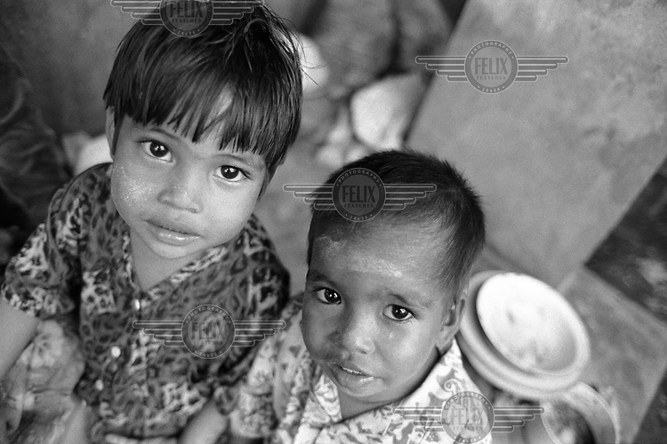 A portrait of two homeless children in the grounds of a Buddhist monastery.