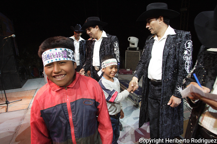 Triqui Native children greet the Grupo Exterminador narcocorrido music group during a party in the Yosoyuxi village, in the Triqui region of Oaxaca, November 18, 2005. The political violence has been increased by the paramilitary groups like UBISORT in the Triqui region, where they ambushed an humanitarian caravan and killing two people on APril 27, 2010.  Photo by Heriberto Rodriguez