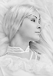 Profile of young lady with big eyes looking away, lying on the white tulle material, monochromatic