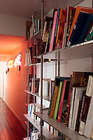 In this corridor the bright orange wall highlights a work of art by Jason Rhoades whilst functional yet stylish aluminium bookshelves make maximum use of available space