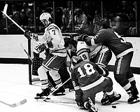 Seals vs Detroit Red Wings 1975 action:<br />Seals Dave Gardner and Jim Moxey, Wings Bryan Watson and Jean Hamel. (photo/Ron Riesterer)