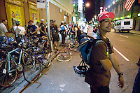 3 July 2005 - New York City, NY, USA - &quot;Junjun&quot; (R) waits for riders to arrive at an alleycat checkpoint on 43rd street in New York City, USA, July 3rd 2005, as other riders take a break from the race and share beers and jokes. Alleycats are urban cycle races held informally - without notification of the authorities - on open roads and in real traffic, to simulate the messenger's working conditions. Photo Credit: David Brabyn<br />