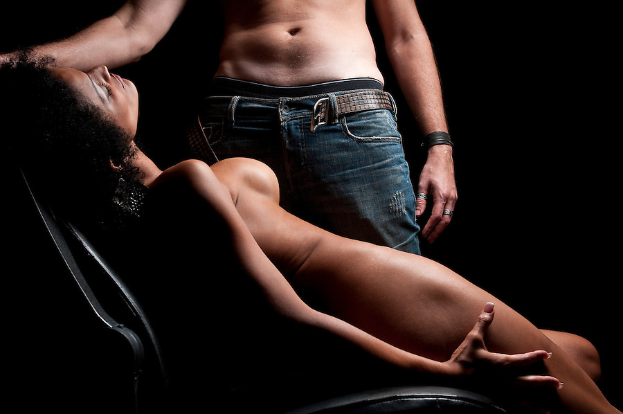 Couple in dim light, very erotic foreplay.