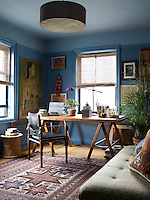 The desk and chair in the study are by Richard Wrightman and the desk lamp is by Brunno Jahara. Below a drum shade by Broome Lampshades is a custom-made daybed upholstered in a silk by Robshaw and the portrait and vintage rug are from India. The window shades are of Cambodian silk