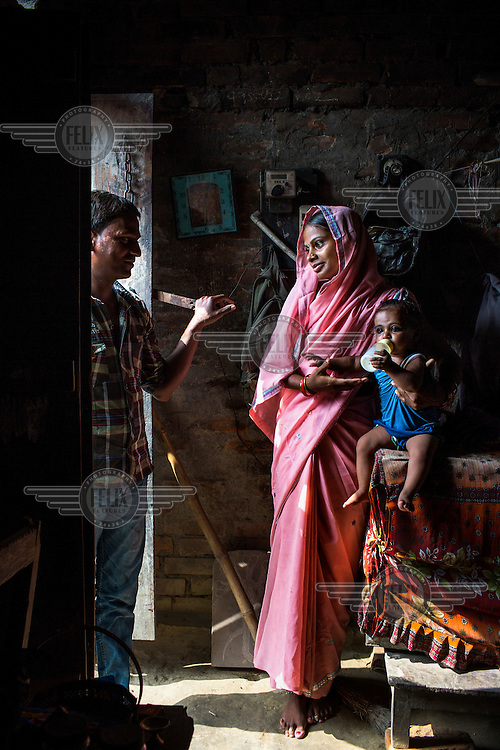 21 year old Seema Devi with her husband Vinay Paswan (22) and their nine month old daughter, Vaishnavi Kumari in the small room of their hut in Shivpur Hariyya village.