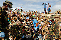 Rescue workers retrieve the body of a five-year-old boy near his house destroyed by Typhoon Haiyan in the town of Tanauan November 20, 2013. The Philippines and international armed forces and aid agencies are struggling to get help to devastated areas due to the extent of the destruction, which has left four million people displaced, threatening Aquino's reforms that have helped transform the country into one of Asia's fastest-growing emerging economies.