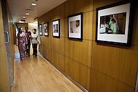 Colleagues walk down the passageway lined with photos of projects at the new Bill &amp; Melinda Gates Foundation office in New Delhi, India on 17th December 2010. Photo by Suzanne Lee for Gates Foundation