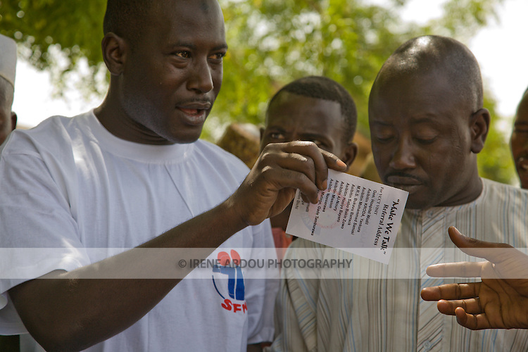 A Society for Family Health (SFH)-trained HIV/AIDS prevention volunteer talks to men in Yankaba market in Kano, Nigeria, HIV counseling and testing services, showing them a referral card that lists counseling and testing sites.  The   Society for Family Health (SFH) is Nigeria's largest indigenous non-profit and affiliate of the international social marketing organization, Population Services International (PSI).