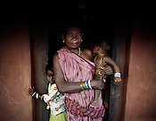 An old Kondh woman is seen with her grand children outside her hut in Ijurupa village that is few metres from the boundary wall of the refinery and causes obstruction of expansion as it falls inbetween the land that has already bought by Vedanta. The villagers are resisting and have decided not to sell the land to the company at any cost.