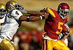 USC's Reggie Bush fights off UCLA's Jarrad Page for extra yardage at the Los Angeles Memorial Coliseum on December 3, 2005.