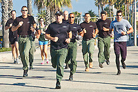 The Santa Monica Police SWAT Team run along the Santa Monica boardwalk while testing in their bi-yearly qualifier on Wednesday, June 6, 2012. The SWAT team was doing the Crossfit Murph Workout which consists of a 1 mile run, 100 pull-ups, 200 push-ups and 300 squats that needs to be completed  in less than one hour.