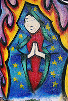 An image of the Virgin of Guadalupe appears calmly impervious to the flames in a mural outside a tattoo shop in Santa Fe, New Mexico