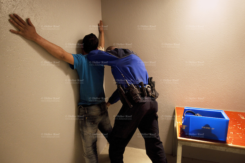 Switzerland. Geneva. A police officer is strip searching a prisoner in a cell at the Paquis police station. The man was arrested while selling drugs in the streets. The inmate is an arab man from the Maghreb area. A strip search is a practice of searching a person for weapons or other contraband suspected of being hidden on their body or inside their clothing by requiring the person to remove some or all of his clothing. The strip search is a mandatory procedure which requires legal authority. It is done by a police officer once a person is arrested and locked in a cell. A police station or station house is a building which serves for police officers. The building contains temporary holding cells and interview/interrogation rooms. 19.03.12 © 2012 Didier Ruef