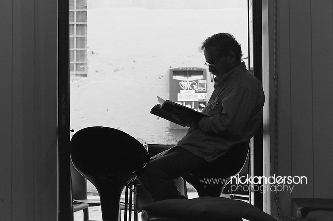 A man sits reading a book in the open second doorway of the Nick Nowego Cafè on Via della Paglia, Rome, silhouetted by the daylight outside (Nick Anderson)