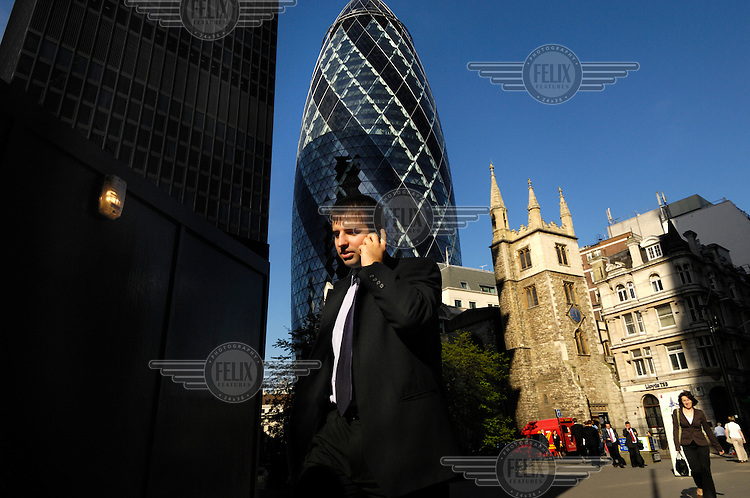 A businessman talks on his mobile phone in the City of London close to the Swiss Re building designed by British architect Sir Norman Foster, colloquially known as 'the Gerkin', and officially as 30 St Mary Axe.
