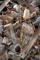 Old pile of rusty screw-top food jars in a dump