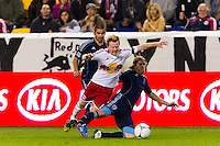 Chance Myers (7) of Sporting Kansas City trips up Dax McCarty (11) of the New York Red Bulls. The New York Red Bulls and Sporting Kansas City played to a 0-0 tie during a Major League Soccer (MLS) match at Red Bull Arena in Harrison, NJ, on October 20, 2012.