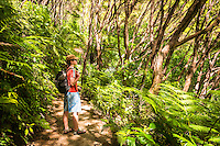 Young woman hiking on Abel Tasman Coast Track, Abel Tasman National Park, Nelson Region, South Island, New Zealand