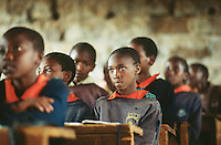 Kenya. Rift Valley Province. Mwenja. Primary school. Classroom. Students, girls and boys, listens to their teacher's lesson.The arms are laid on a wood desk . The pupils are wearing a green, blue and orange uniform. © 2004 Didier Ruef
