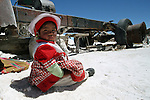 A girl sits while her mother works on a salt mine in Uyuni. Since 2010, Bolivian state-run mining company Comibol has been exploring lithium reserves in the Salar de Uyuni, the world's largest salt flat. The Salar de Uyuni sits at 3,600 meters above sea level and has a total surface area of 10,582 square kilometers.