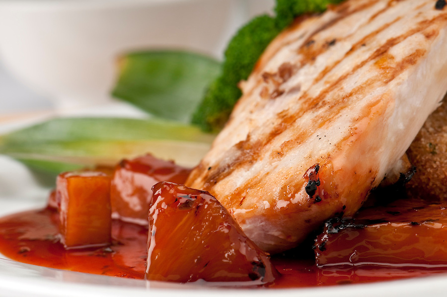 Close up of plate of Mahi Mahi, severd with vegetables, pineapple and soy sauce.