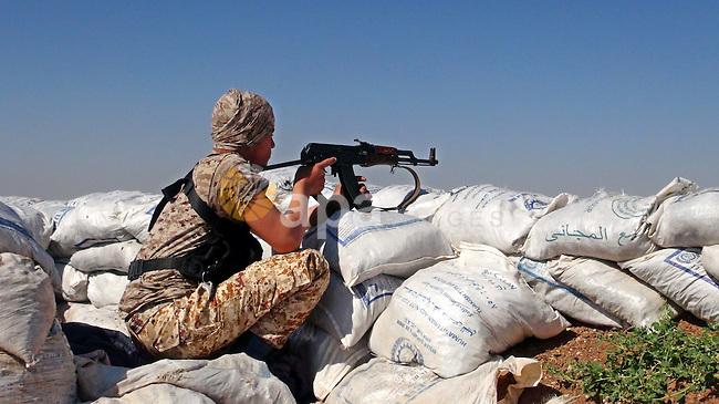 A fighter from the Free Syrian Army's Al-Tawhid Brigade takes a position at the border with Dabiq city, the stronghold of the ISIS fighters, in the Mare' city in the north of Aleppo, on June 30, 2015. Photo by Ameer al-Halbi