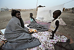 A displaced woman and her children awake in the morning after sleeping outside on the ground in front of their hut in Agok, a town in the contested Abyei region where tens of thousands of people fled in 2011 after an attack by soldiers and militias from the northern Republic of Sudan on most parts of Abyei. Although the 2005 Comprehensive Peace Agreement called for residents of Abyei--which sits on the border between Sudan and South Sudan--to hold a referendum on whether they wanted to align with the north or the newly independent South Sudan, the government in Khartoum and northern-backed Misseriya nomads, excluded from voting as they only live part of the year in Abyei, blocked the vote and attacked the majority Dinka Ngok population. The African Union has proposed a new peace plan, including a referendum to be held in October 2013, but it has been rejected by the Misseriya and Khartoum. The Catholic parish of Abyei, with support from Caritas South Sudan and other international church partners, has maintained its pastoral presence among the displaced and assisted them with food, shelter, and other relief supplies.