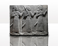 Picture & image of a Neo-Hittite orthostat of 3 warriors from the legend of Gilgamesh from Karkamis,, Turkey. Ancora Archaeological Museum. The warrior on the far left holds a spear in one hand and the branch of a tree in the other. The middle warrior has a clenched fist an carries an impliment over his shoulder. The warrior on the far right carries a saff. All 3 are wearing swords.  4