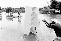 "Mozambique. Province of Gaza. Chokwe. The Limpopo river has flooded the whole town.""Tercero Barrio"", one of its districts, was heavily flooded and its population suffered the largest destruction and losses. A man washes the mud away from his cupboard. © 2000 Didier Ruef"