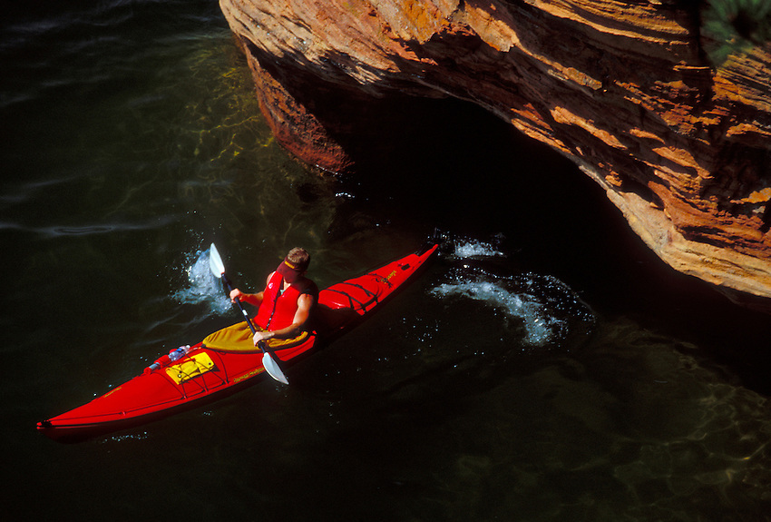 A KAYAKER EXITS A SEA CAVE AT SQUAW POINT IN THE APOSTLE ISLANDS NATIONAL LAKESHORE NEAR BAYFIELD, WISCONSIN.