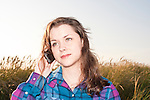 Young adult in tall grass using phone