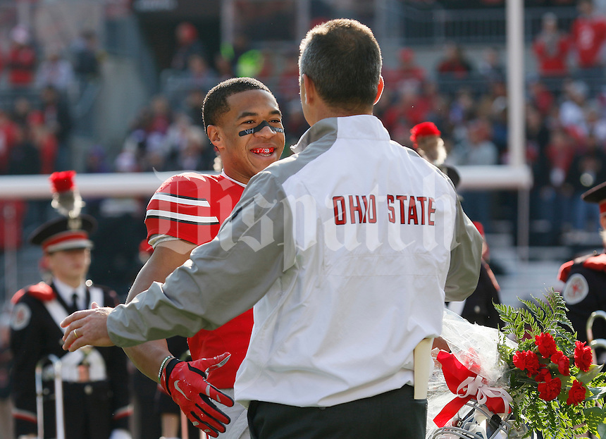 Ohio State Buckeyes wide receiver Evan Spencer (6) hugs head coach Urban Meyer as he takes the field for Senior Day festivities prior to the NCAA football game against the Michigan Wolverines at Ohio Stadium on Nov. 29, 2014. The Buckeyes won 42-28. (Adam Cairns / The Columbus Dispatch)