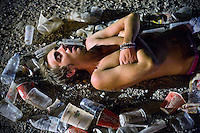BENIC&Agrave;SSIM, SPAIN - A festival goer sleeps on gravel in the festival site. ..Described by some as a Mediterranean Glastonbury, the Festival Internacional de Benic&agrave;ssim (FIB) is the largest music festival outside the UK to target British visitors. In 2010, seven of the eight main headline slots were filled by English bands...A small coastal town of 13,000 inhabitants, Benic&agrave;ssim hosted some 200,000 visitors in 2009, with 40% of those believed to be coming from the UK. In 2010, attendances fell to 127,000 visitors but the percentage of UK visitors is believed to have risen.