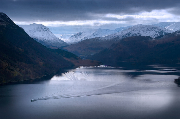 Snow capped mountains rising above a lake in winter with a boat creating ripples