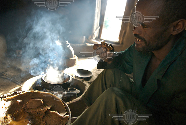 Yimer Seshigue eating injera in his hut in the Hanamerant area of Meket.