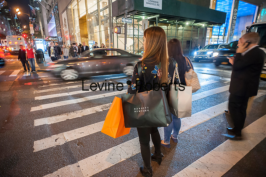 A woman waits at an intersection in New York holding shopping bags with her various purchases on Tuesday, October 4, 2016. (©Richard B. Levine)