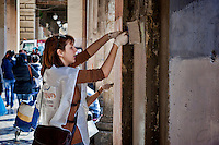 Volunteers clean the Piazza Vittorio.<br /> &quot;Wake up Roma ', the great collective mobilization promoted by Retake and Luiss EnLabs for the decorum of the city against the deterioration and abandonment. About three thousand volunteers with scrapers and brushes in hand they removed posters and stickers, clean walls and poles, they cleaned up gardens and flower beds, driveways and sidewalks. Interventions to Piazza Vittorio, Porta Maggiore, Villa Paganini and place Anco Marzio in Ostia. Rome, Italy 12th March 2016