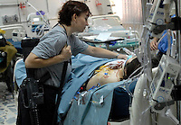 1st Lt. Kathleen Williams, 37 of Ft. Sill, OK, visits a female patient with a  shot wound in the Intensive Care Unit of the 10th Combat Support Hospital in Baghdad. William was off duty but said that she choose to visit the victim to remind her that she had a lot to live for. The patient succombed to her injuries and died a few hours later. March, 8, 2006. (James J. Lee / Army Times)