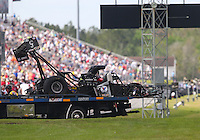 Mar 14, 2015; Gainesville, FL, USA; The  dragster of NHRA top fuel driver Larry Dixon is taken back to the pits on a flat bed tow truck after his car broke in half and crashed during qualifying for the Gatornationals at Auto Plus Raceway at Gainesville. Dixon walked away from the incident. Mandatory Credit: Mark J. Rebilas-USA TODAY Sports