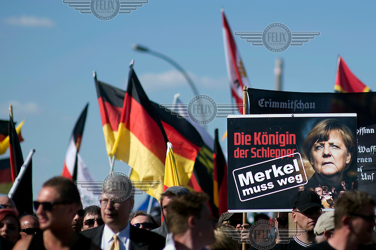 Protestors with a placard that reads: 'Merkel Must Go', at a rally of German right-wing organisations including the NPD and the populist PERGIDA (Patriotic Europeans Against the Islamisation of the Occident) movement. The demonstrators, marching under the slogans 'We For Germany' and 'Merkel Must Go', made their way through the government quarter.