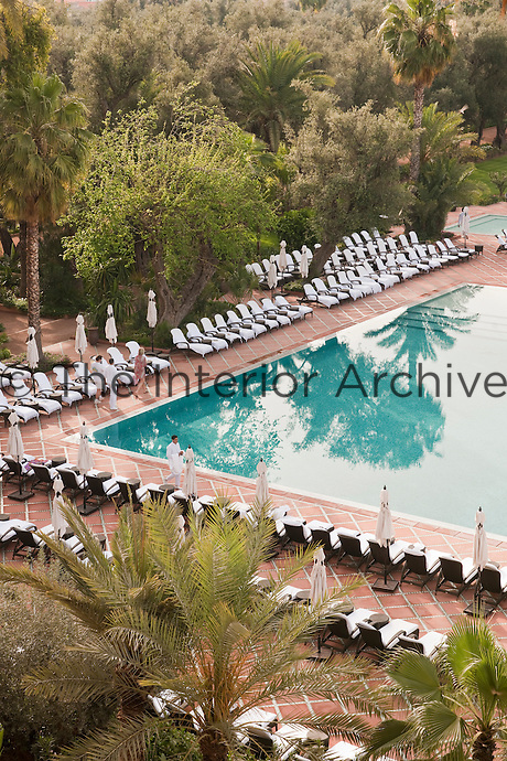 Rows of sun-loungers surround the outdoor swimming pool